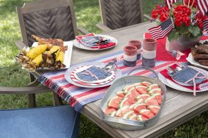 Outdoor dining table set with barbecue foods and 4th of july decorations.