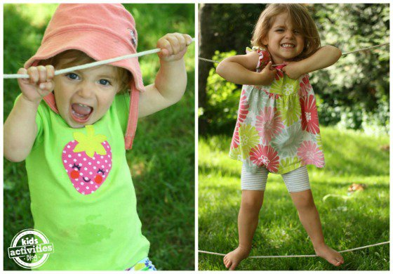 Two little girls playing on a DIY tight rope in their backyard.