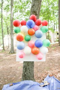 Balloon darts game being played outside on a tree
