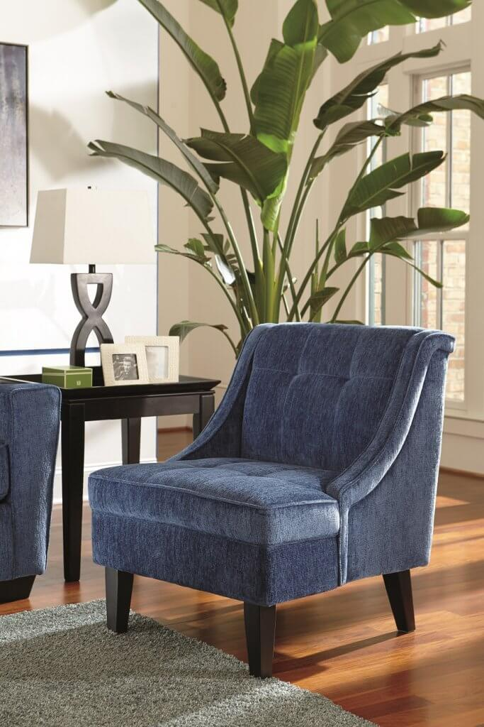 Blue fabric accent chair with an end table and lamp, and bamboo tree next to it.