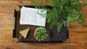 bohemmian tray with books, greenery and sculptures.