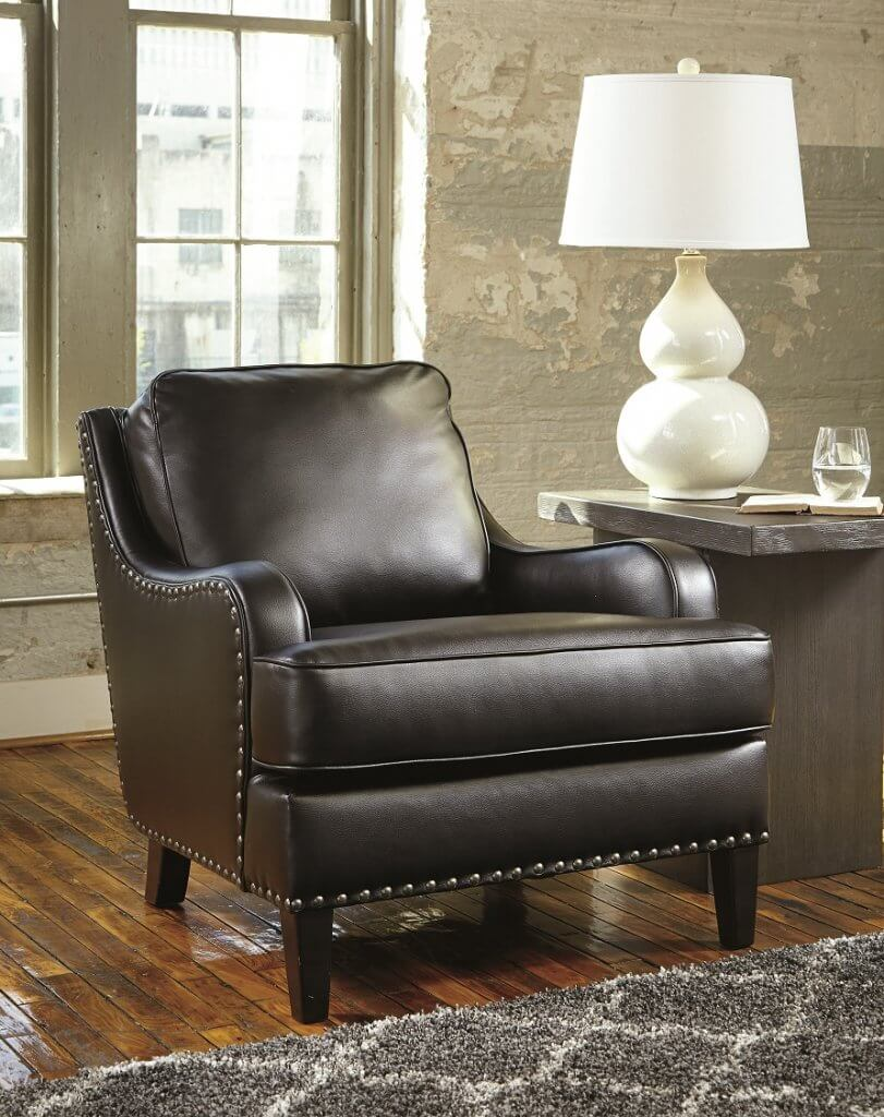 brown leather lounge chair with a side table next to it with a white lamp.