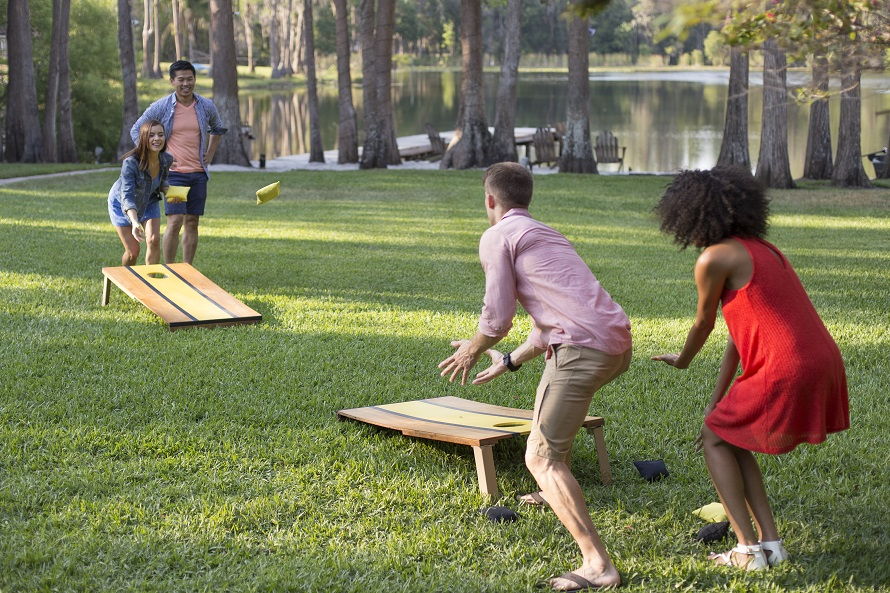 Young people playing corn-hole outside during 4th of july.