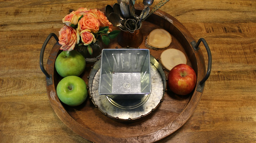 Round tray with farmhouse touches like fresh fruit, wood carvings and aluminum bowls.