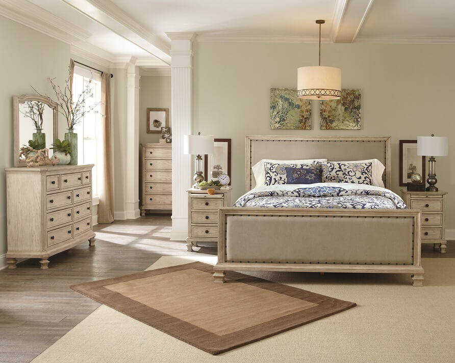 Farmhouse chic befroom with bed, dressar and nightstand with rustic artwork and a neutral rug.