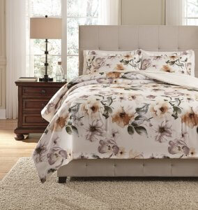 water colored floral patterned white comforter set on a bed with a white shag rug on the floor in front.