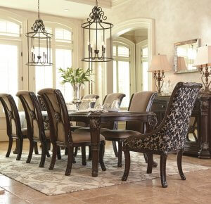 brown traditional dining room set with server and upholstered chairs and two large chandeliers above.