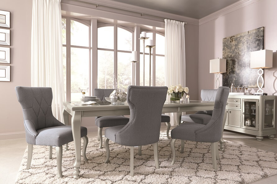 Gray sleek and glamorous dining room table with a gray and white patterned rug.