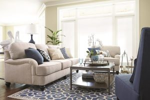 Sofa, oversized chair and armless chair with a coffee table on a patterned blue rug.