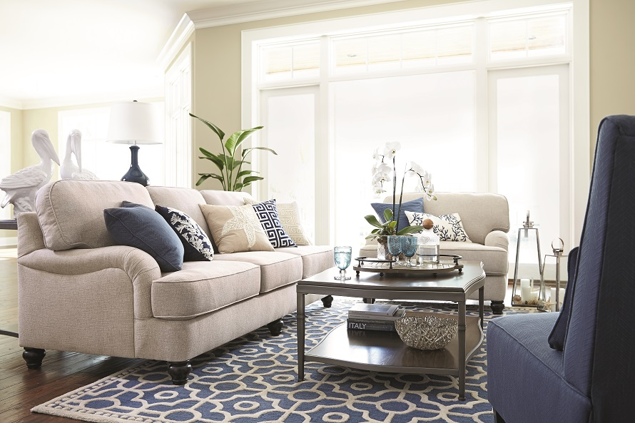 coastal style living room. Sofa  oversized chair and armless with a coffee table on patterned blue rug Coastal Living Furniture And Decor Ideas Ashley HomeStore