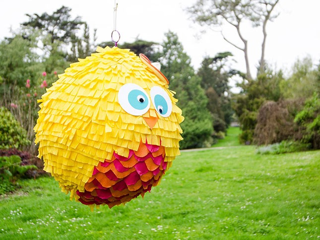 paper mache pinata hanging from a tree in the backyard