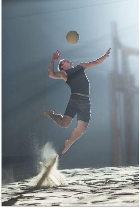 image of a professional volleyball player in the sand spiking the ball.