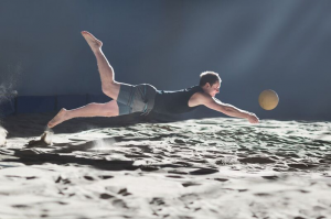 Professional volleyball player diving for a ball on a beach volleyball court.