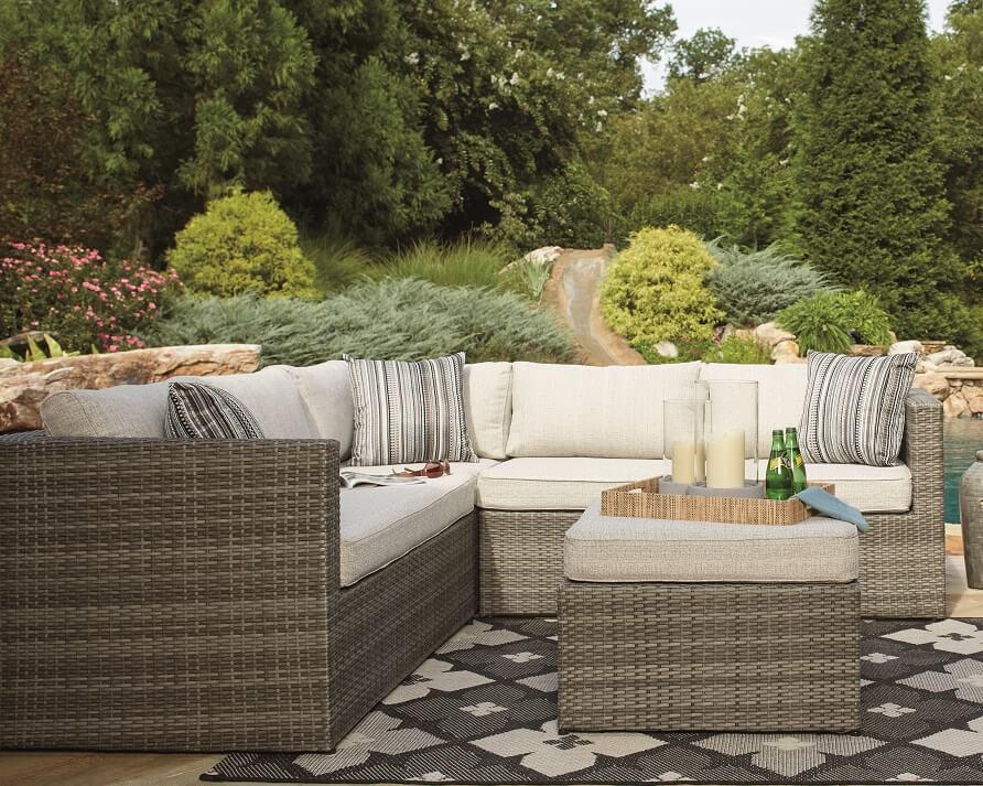 Outdoor sectional with matching pillows and table in a garden.