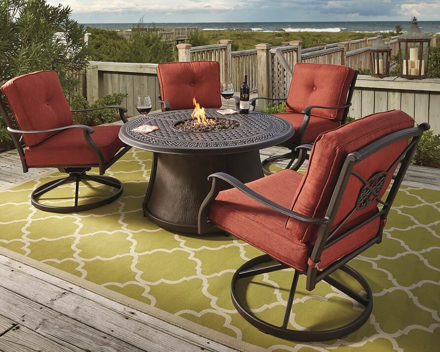 outdoor table and chair with built in fire place ona dock overlooking the beach