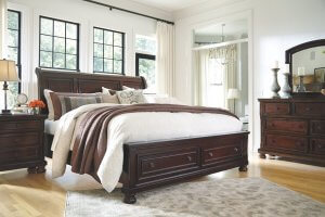 Brown wooden contemporary bed in a white room with windows behind the bed and a lush comforter.