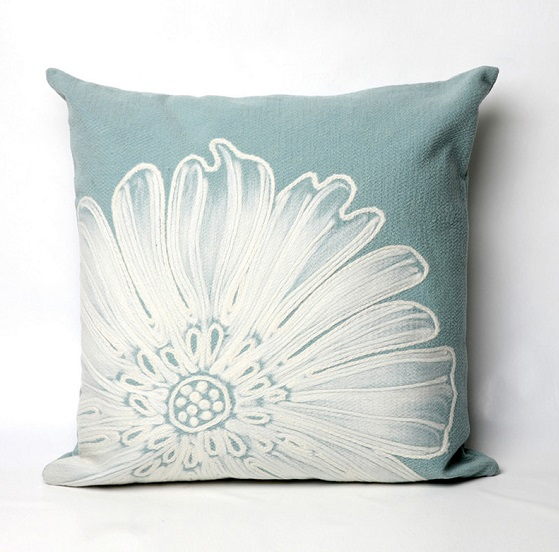 Light blue pillow with a white flower printed on it.
