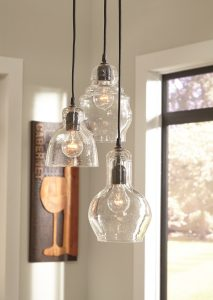 Light fixture trio of seeded glass pendants with eclectic shapes hanging from the ceiling.