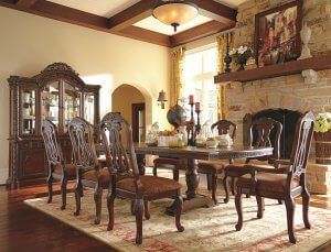 Formal dining room and chairs with intricate details in the wood in a rustic like setting.