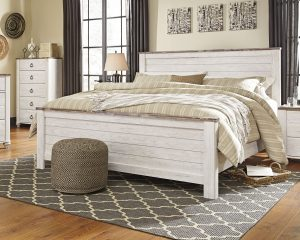 White coastal bed with distressed wood with tan bedding a geometric rug and a pouf on the rug.