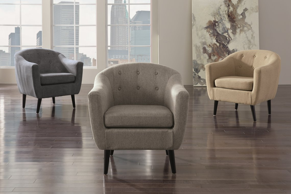multiple tufted accent chairs in an empty room.