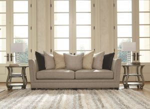 Cream colored sofa with layers of pastel colored pillows with a striped fluffy rug in front.