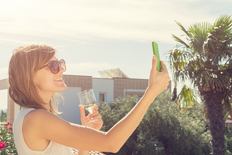 Smiley girl using cellphone and drinking wine outdoors.