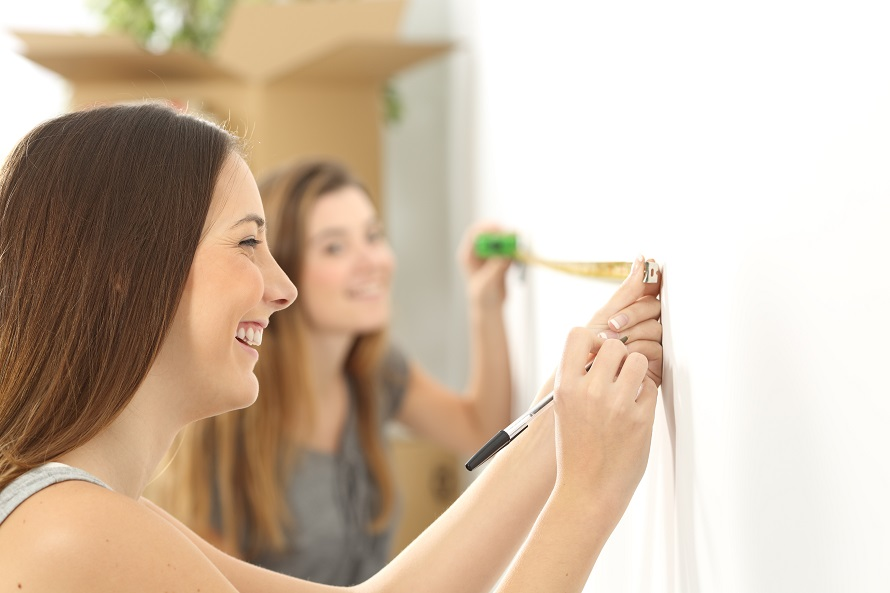 Two roommates measuring with a measure tape in a wall helping each other while they are moving home
