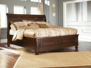 A brown traditional queen sleigh bed with drawers for storage.