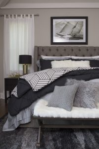 Nautical and coastal decorated bedroom with fluffy pillows, blue and gray colors and lots of accessories.