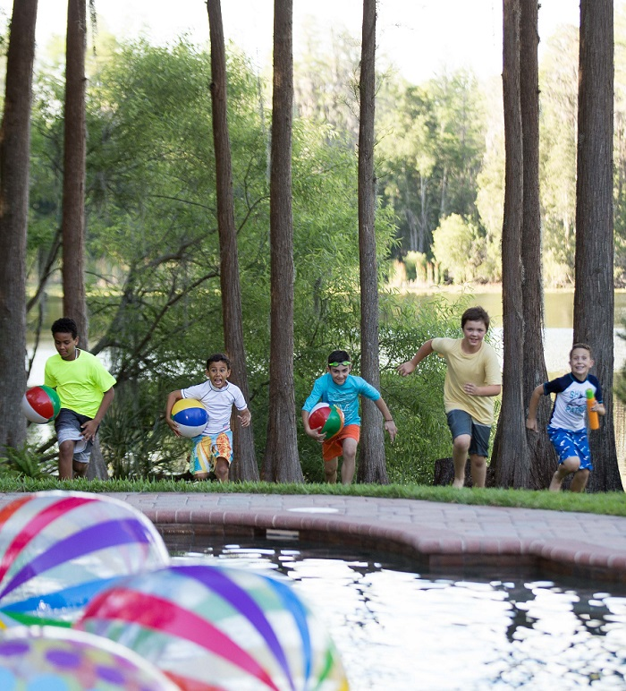 Several young boys jumping into a pool filled with beach balls.
