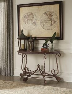 Dark brown wooden console table with global decor on top.