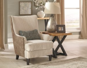 contemporary chair in a neutral room with a side table and lamp next to it.