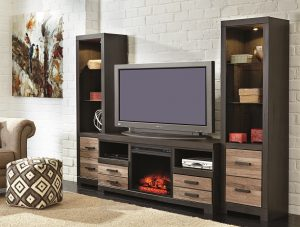 two tall shelving units sideline this TV stand on this entertainment center set with fireplace insert