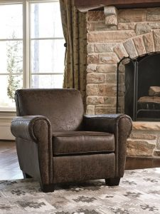 leather like brown chair in front of a fireplace.