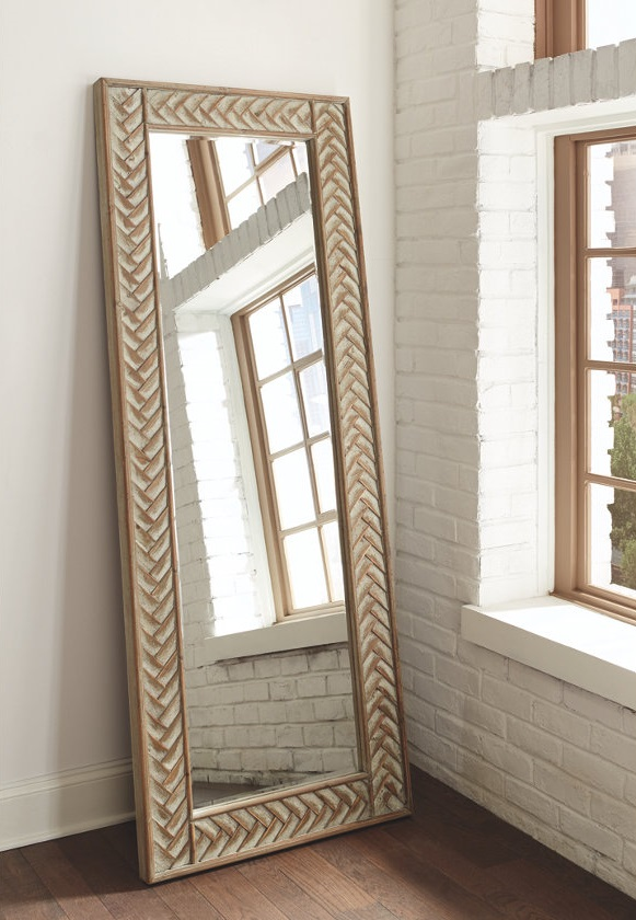 Wall mirror with cold accents around the trim sitting up against a white wall.