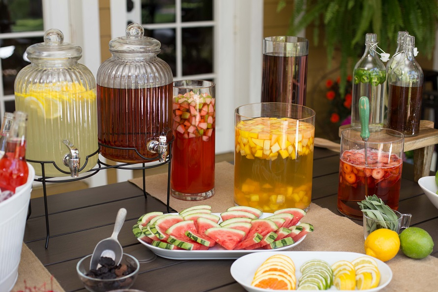 Drink bar set up outside during summer on a patio filled with various fruit juices.