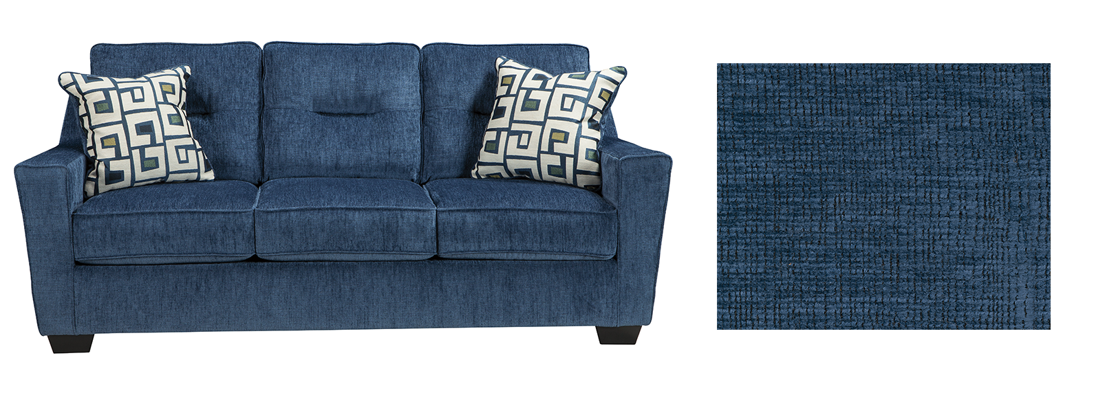 Blue sofa with aztec designed pillows with a fabric splotch next to it.