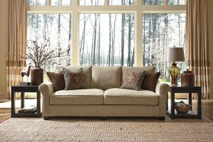 Brown cushioned sofa with Moroccan pillows on top with rustic background.