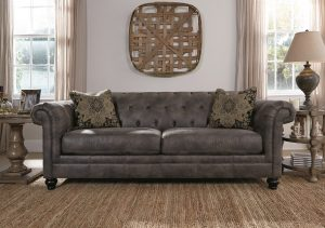 Button Tufted Elegant Worn Gray Leather Look sofa with morrocan designed pillows with brown wood wall art on the wall.