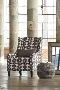 Urban and industrial accent chair in a industrial room with a gray pouf next to the chair.