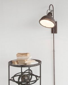 Industrial mounted lamp on a wall shining down on a side table.