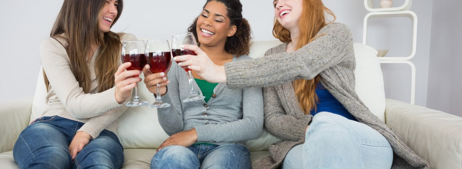Cheerful young female friends toasting wine glasses on sofa at home
