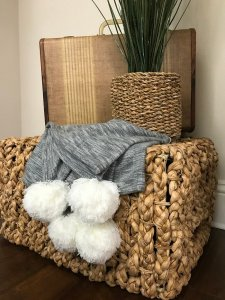brown basket with a throw blanket holding working items.
