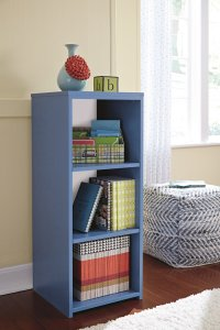 blue youth bedroom bookcase next to a blue and white pouf