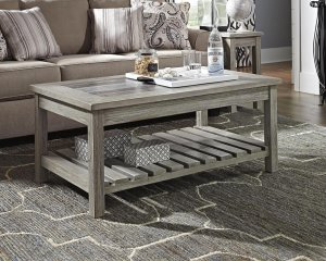 whitewashed wood coffee table with decor on top.
