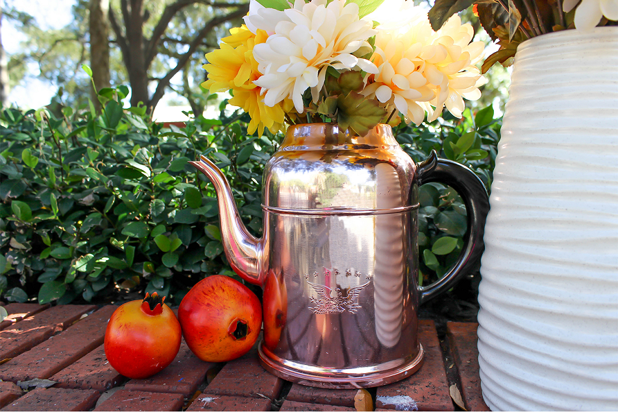 fall flowers displayed in a watering can outside among other fall nature elements.