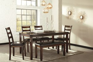 Brown contemporary dining room table with sunburst mirrors on the wall.
