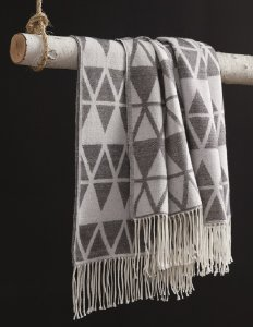 patterned threaded weave blanket with tribal patterns hanging on a tree branch