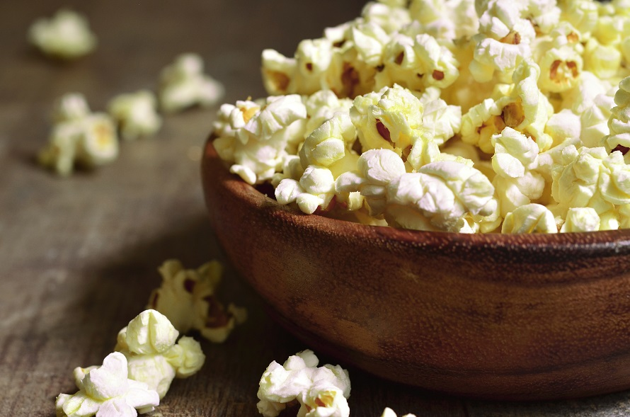 A bowl of popcorn on a wooden table.